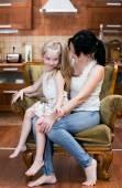 Мать и ее маленькая дочь, сидя в кресле — Стоковое фото