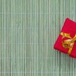 Decoratively wrapped gift box on bamboo background — Stock Photo #59862649