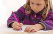 Child draws the picture with color pen. Serious, absorbed face — Stok fotoğraf