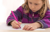 Child draws the picture with color pen. Serious, absorbed face — Photo