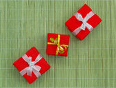 Three decoratively packed gifts on the green bamboo mat — Stock Photo