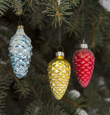 Winter composition with toy cones suspended on natural christmas tree — Stock Photo
