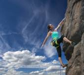 Elegant female climber and cloudy sky — Stock Photo