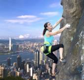 Female rock climber over the city skyline — Stock Photo