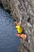 Young male rock climber hanging over the water and looking up — Fotografia Stock
