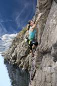Female extreme climber conquers steep rock over the impressive rocky beach — Stock Photo