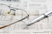 Business newspaper and glasses — Stock Photo