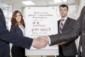 Two young corporate trainers welcome participants of the training — Stock Photo