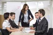 Energetic corporate manager instructs her team — Stockfoto