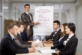 Young corporate coach and audience — Stock Photo