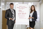 Male and female instructors welcomes attendants pointing on the flip chart — Stock Photo