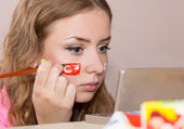 Young female making up her face with Turkish flag — Stock Photo