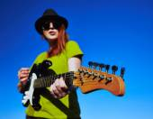 Stylish guitar in the hands of female artist — Stock Photo