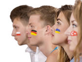 Side view of faces of four teenagers with flags on faces — Stockfoto