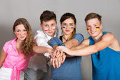 Four young people joining hands — Stock Photo