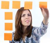 Young lady attaches sticker to the board — Stock Photo