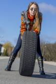 Female biker rolls big wheel — Stock Photo