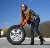 Leggy beautiful female holds big wheel — Stock Photo