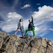 Two female climbers observing the landscape from summit — Stock Photo #72119021