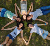 Five young ladies lounging on grassy lawn — Stok fotoğraf