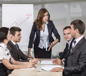 Female manager energetically talks to her team. Four people sit around the table covered by paperwork. Flip chart and open space office on the background — Stockfoto
