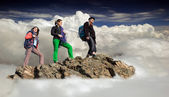 Group of climbers stays on the cliff surrounded with the sea of clouds — Stock Photo