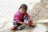Little baby girl of Chinese hani minority plays in puddle on road — Stock Photo
