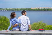 Young couple on parapet looking sideward — Stock Photo