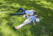 Young man and woman napping on grassy lawn — ストック写真