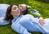 Young man and woman napping on grassy lawn — Stock Photo