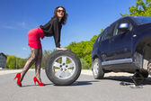 Leggy female changing wheel of car — Stock Photo