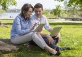 Students with electronic devises sitting on stone — Stock Photo