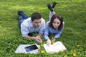 Grass and flowers and two people reading — Foto de Stock