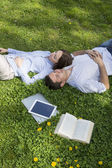 Young man and woman napping on grassy lawn — Stok fotoğraf