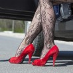 Постер, плакат: Feet of stylish female driver walking out of car