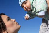 Mother and baby on blue sky background — Stock Photo