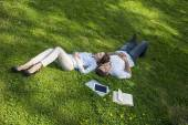 Two people napping on grassy lawn — Stock Photo