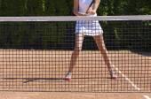 Slim legs of female tennis athlete behind fishnet barrier — Stock Photo