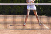 Slim legs of female tennis athlete behind fishnet barrier — Stockfoto