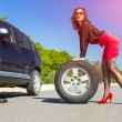 Sexy dressed female body holding car tire — Stock Photo #77522372