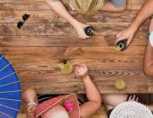 Group of relaxed people drinking cocktails at wooden table — Stock Photo