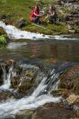 Flow of transparent pure mountain creek water and people on background — Stock Photo