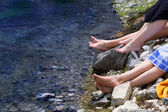 Mountain lake and female feet — Stock Photo