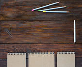 Dark Brown Wooden Desk with Sketchbooks and Pencils — Stock Photo