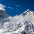 Постер, плакат: Majestic View of High Altitude Snowbound Mountain Peaks with Glaciers Rocks Snow Clouds and Blue Sky