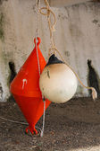 Orange conical buoy and white spherical buoy hanging outside wat — Zdjęcie stockowe