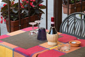 Wicker wine bottle on a tuscan restaurant table — Stock Photo