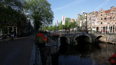 View on the water of Amsterdams canal traffic with its many pleasure craft and bridges — Vídeo de stock