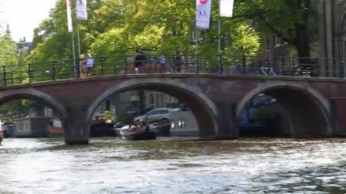 View on the water of Amsterdams canal traffic with its many pleasure craft and bridges — ストックビデオ