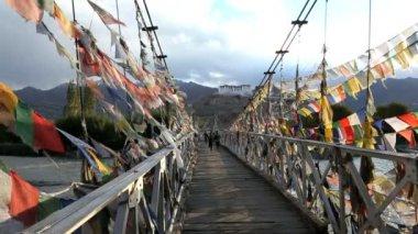 School children crossing bridge covered in Prayer flags — Stock Video